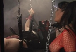 The chained man has a black-haired hostess riding him in the dungeon